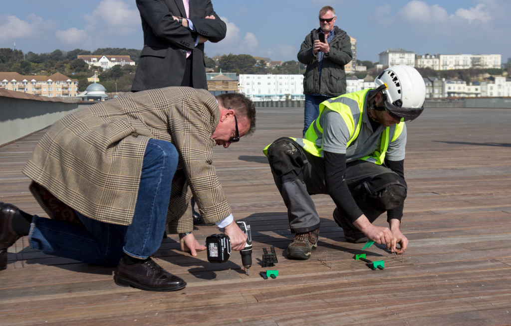 Suggs lays the pier's last plank. Photo Credit: George Palmer